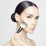 Face Makeup. Studio fashion photo of beautiful young lady applying blush. Beauty and care. Extension eyelashes. Spa salon. Perfect face makeup Royalty Free Stock Photos