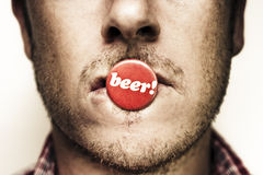 Face Of A Man With Beer Badge Royalty Free Stock Image