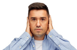 Face of man covering his ears with hands Stock Photography