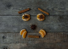 Face with mandarin, anise and cinnamon on wooden background Stock Images
