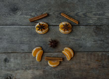 Face with mandarin, anise and cinnamon on wooden background.  Stock Image