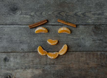 Face with mandarin, anise and cinnamon on wooden background Royalty Free Stock Images