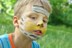 Face mask. Portrait of a young boy with a face paited  mask Royalty Free Stock Photo