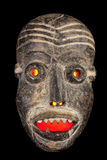Face mask with red evil eyes. Wooden carved African tribal mask, dark wood with painted face. Isolated on black  background. Congo, Africa Royalty Free Stock Photos