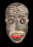 Face mask with red evil eyes. Wooden carved African tribal mask, dark wood with painted face. Isolated on black  background. Congo, Africa Royalty Free Stock Images