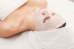 Face mask, spa beauty treatment, skincare. Face mask, spa beauty treatment. Woman applying facial clay mask at spa salon, skincare Royalty Free Stock Photo