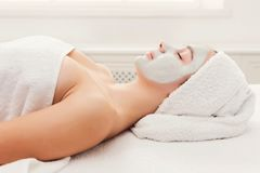 Face mask, spa beauty treatment, skincare. Face mask, spa beauty treatment. Woman applying facial clay mask at spa salon, skincare, copy space, side view Royalty Free Stock Photography