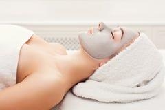 Face mask, spa beauty treatment, skincare. Face mask, spa beauty treatment. Woman applying facial clay mask at spa salon, skincare, top view, overhead Stock Image