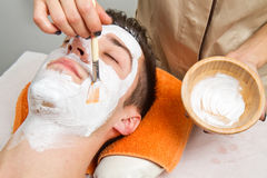 Face mask. Therapist applying a face mask to a beautiful young man in a spa using a cosmetics brush royalty free stock photography