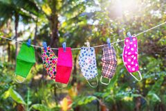 Free Face Masks With Different Style Prints Hang And Dry On Clothespins Outdoors At Sunset Stock Image - 179929351