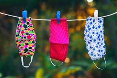 Free Face Masks With Different Style Prints Hang And Dry On Clothespins Outdoors At Sunset Stock Images - 182304814