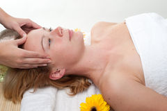 Face massage. Beautiful young woman having a face massage in wellness centre - girl in spa Royalty Free Stock Image
