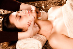 Face massage. Woman enjoy in face massage in spa salon Royalty Free Stock Photography