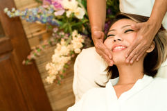 Face Massage. A young Asian woman having a face massage in a beauty salon Stock Photos