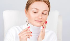 Face massage. Beautiful woman getting massage face using roller massage stock photo