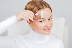 Face massage. Beautiful woman getting massage forehead using roller massage royalty free stock photo