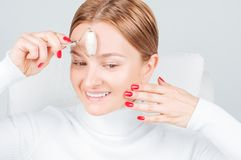 Face massage. Beautiful woman getting massage forehead using roller massage royalty free stock photos