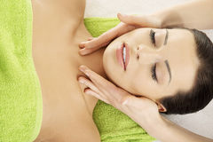 Face massage therapy at spa saloon. Beautiful young relaxed woman enjoy receiving face massage therapy at spa saloon Royalty Free Stock Photography