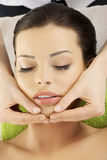 Face massage therapy at spa saloon. Beautiful young relaxed woman enjoy receiving face massage therapy at spa saloon Stock Photo
