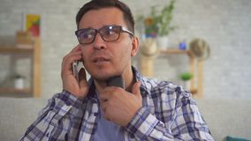 Portrait of middle-aged man in home answering a phone call uses Speech Aid problems with ligaments