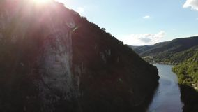 Face in the mountain stone. Aerial shoot opening from rock to river and mountains stock video footage