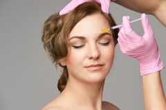Face needle injection. Young woman cosmetology procedure. Doctor gloves. Brow between stock photography