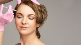 Face needle injection. Young woman cosmetology procedure. Doctor pink gloves. Brow royalty free stock photo