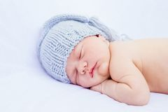 Face of newborn baby sleeping wearing grey hat and panties stock photos