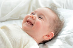 Face of a newborn baby smile. In his baby cot. Concept photo of newborn, baby, mother, motherhood, parenting and lifestyle Stock Image