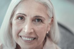 Face of a nice aged woman. Pleasant smile. Face of a nice positive aged woman while smiling and looking at you stock photos