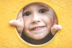 Face Of Small Child Girl Looking Through A Hole In A Play Equipment Outdoors. Yellow Background. Happy Childhood Concept. Royalty Free Stock Image