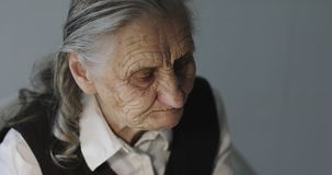 Face of an old woman with deep wrinkles drinking coffee. Grandmother sits in the office and has lunch stock video footage