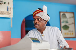 Face of older indian waiter of popular indian cafe with colorful interior Royalty Free Stock Images