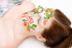 Face pack. Girl with fruit and cream Royalty Free Stock Image