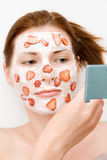 Face pack. Girl with friut and cream face pack looking in the mirror Royalty Free Stock Photo
