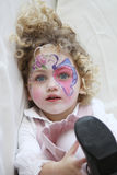 Face paint. Portrait of a young child with her face painted and foot in the air looking towards the camera Royalty Free Stock Image