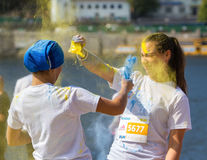 Face in the paint Holi. Ukraine, Kyiv - 08/14/2016. Kyiv color run. Run 5 km from the colors of Holi. Funny girl throw each other in the face paint Holi royalty free stock images