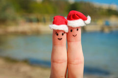 Face painted on the fingers. Happy couple resting on the beach royalty free stock images