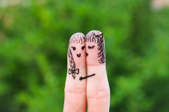 Face painted on the fingers.  woman is kissing his girlfriend on cheek Royalty Free Stock Photo