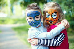Face painted little friends embracing outside. Two face painted little friends embracing outside Royalty Free Stock Images