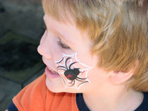Face-painted spider. Little boy with spider-art face painting Royalty Free Stock Image