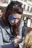 Face Painter. Venice,Italy-February 26, 2011: Environmental portrait of a female street face painter working on Sestiere Castello in Venice during the Venice Stock Photos