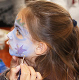 Face painting. A pretty caucasian child getting her face painted Royalty Free Stock Images