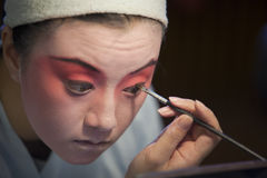 Face-painting. The Beijing opera actress is painting the scenic mask on her face Royalty Free Stock Photo