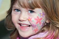 Face painting. Closeup shot of cute little toddler girl with flower face painting Royalty Free Stock Photography