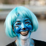 Face painting. Happy young woman with blue face painting and wig representing Knox from Dr Seuss's children's book, Fox in Socks Royalty Free Stock Images