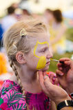 Face-painting. Beautiful blond girl waiting to be face-painted royalty free stock photography