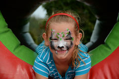 Face painting. Beautiful girl with face painting of black cat poses in the park Royalty Free Stock Images