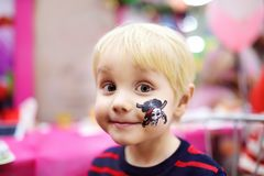 Face painting for cute little boy during kids birthday party. Face painting for cute little boy during kids merriment. Face paint for `Pirates` theme on birthday royalty free stock photos