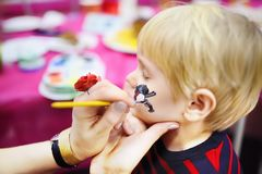 Face painting for cute little boy during kids birthday party. Face painting for cute little boy during kids merriment. Face paint for `Pirates` theme on birthday Royalty Free Stock Images
